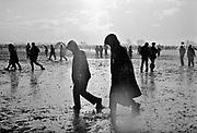 Two hooded individuals walk through the mud and rain. Glastonbury 2005
