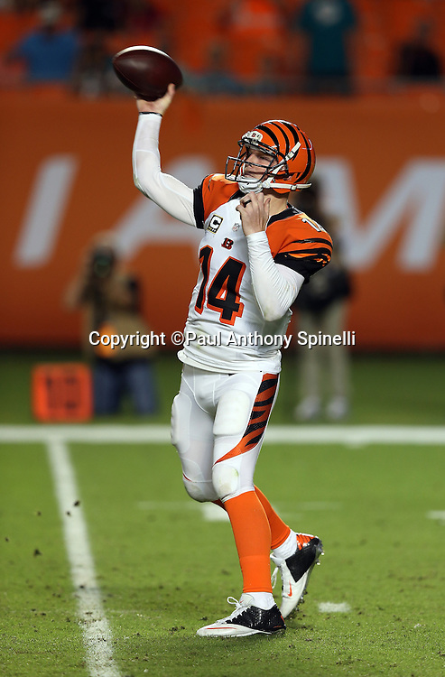 Cincinnati Bengals quarterback Andy Dalton (14) throws a pass good for a first down on the first drive of the third quarter during the NFL week 9 football game against the Miami Dolphins on Thursday, Oct. 31, 2013 in Miami Gardens, Fla.. The Dolphins won the game 22-20 in overtime. ©Paul Anthony Spinelli