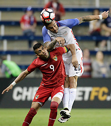 US defender Geoff Cameron (20) heads the ball over Bolivia forward Yasmani Duk (9) in the second half of a men's international friendly soccer match, Saturday, May. 28, 2016, in Kansas City, Kan. The US beat Bolivia 4-0. (AP Photo/Colin E. Braley)