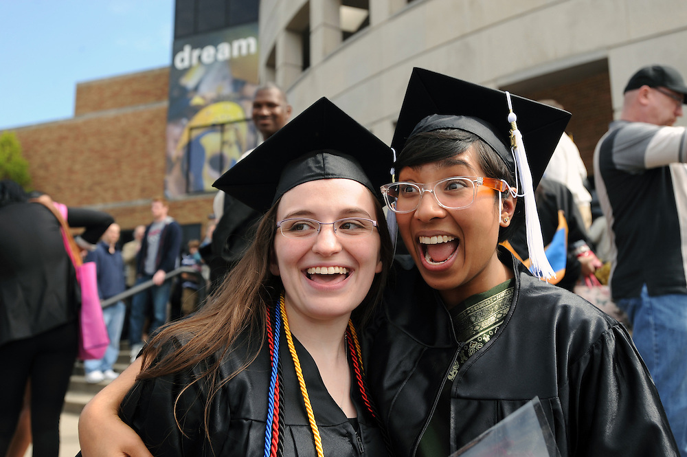 Two Kent State graduates celebrate following morning commencement ceremonies at Kent State University.