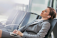 Portrait of businesswoman listening to music on smartphone while sleeping and waiting for boarding in airport