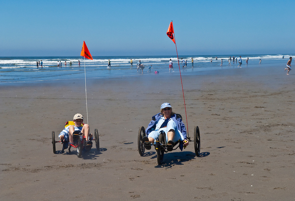 Mother and son riding peddle trikes on the beach at Seaside, Oregon.
