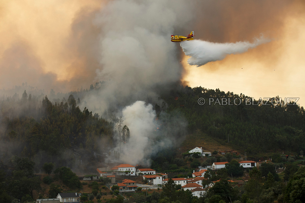 LEIRIA, PORTUGAL - JUNE 20:  A firefighter plane battles a fire after a wildfire took dozens of lives on June 20, 2017 in Mega Fundeira village, near Picha, in Leiria district, Portugal. On Saturday night, a forest fire became uncontrollable in the Leiria district, killing at least 62 people and leaving many injured. Some of the victims died inside their cars as they tried to flee the area.  (Photo by Pablo Blazquez Dominguez/Getty Images)