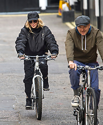 ©  London News Pictures. 10/04/2016. London, UK.  Singer MADONNA (left) leaving her home in central London on her bike, accompanied by security. Madonna was reunited with her son Rocco following a recent court battle over his custody with Madonna's former husband Guy Ritchie. Photo credit: Ben Cawthra/LNP