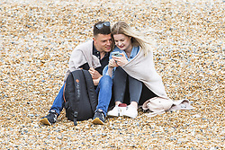 May 26, 2019 - Brighton, East Sussex, United Kingdom - Brighton, UK. A couple cuddle up under a blanket on the beach in Brighton and hove as cooler weather is hitting the seaside resort on the May Bank Holiday Sunday. (Credit Image: © Hugo Michiels/London News Pictures via ZUMA Wire)