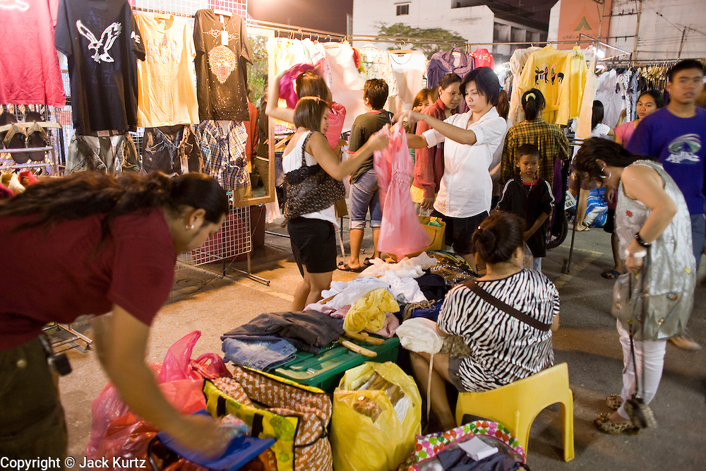21 FEBRUARY 2008 -- KANCHANABURI, THAILAND: People shop for clothes in the night market in Kanchanaburi, Thailand. Thailand's night markets are popular with Thais and tourists alike because they offer bargains in fake designer clothes and watches and a huge variety of inexpensive foods. Photo by Jack Kurtz