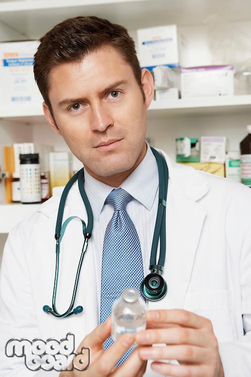 Male doctor holding medication bottle in hospital,portrait