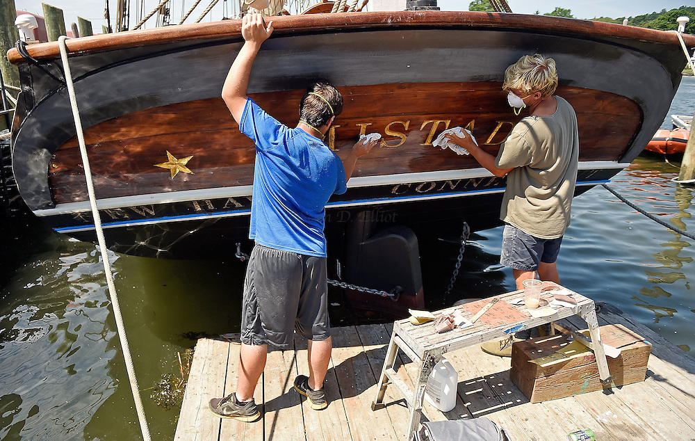 7/25/16 :: REGION :: STAND ALONE :: Joey Luketich, left, and Sam Godfrey apply denatured alcohol to clean up after sanding the transom of the schooner Amistad docked at Mystic Seaport Monday, July 25, 2016. The schooner is in the late stages of a comprehensive refit under the auspices of the new owner, Discovering Amistad, with new sails, rebuilt engines and extensive work on the hull and rigging. (Sean D. Elliot/The Day)