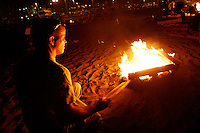 21 June 2008: Ray Brown gets a wood burning bonfire started at tower 9 in Huntington Beach, California early summer night.