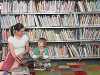 Woman reading book to boy sitting on library floor