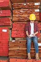 Asian female industrial worker using tablet PC while sitting on stacked wooden planks