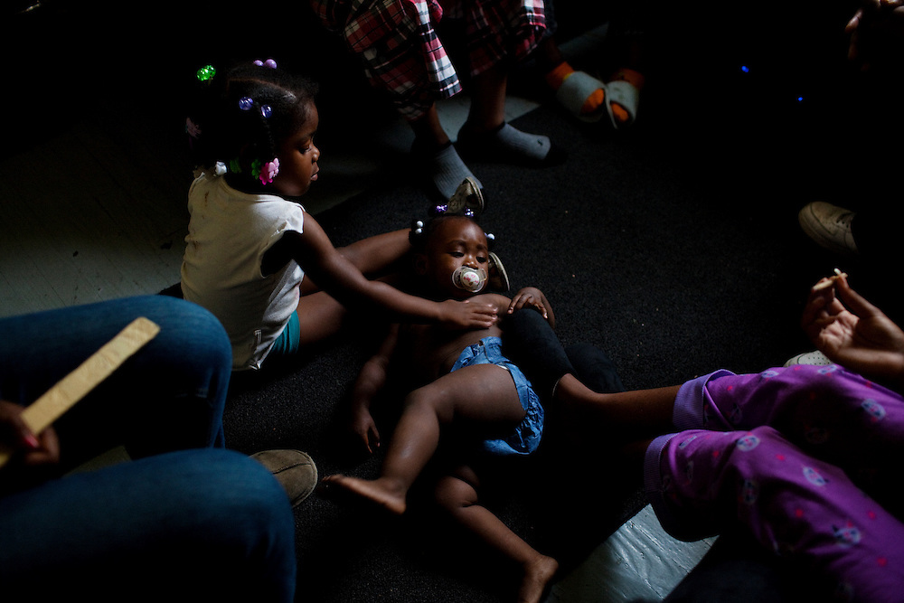 Destinee Benford lies on the floor while a young girl touches her in a friend of her their mom's home as the women sit in a circle, smoking blunts in the Baptist Town neighborhood of Greenwood, Mississippi on May 25, 2011.