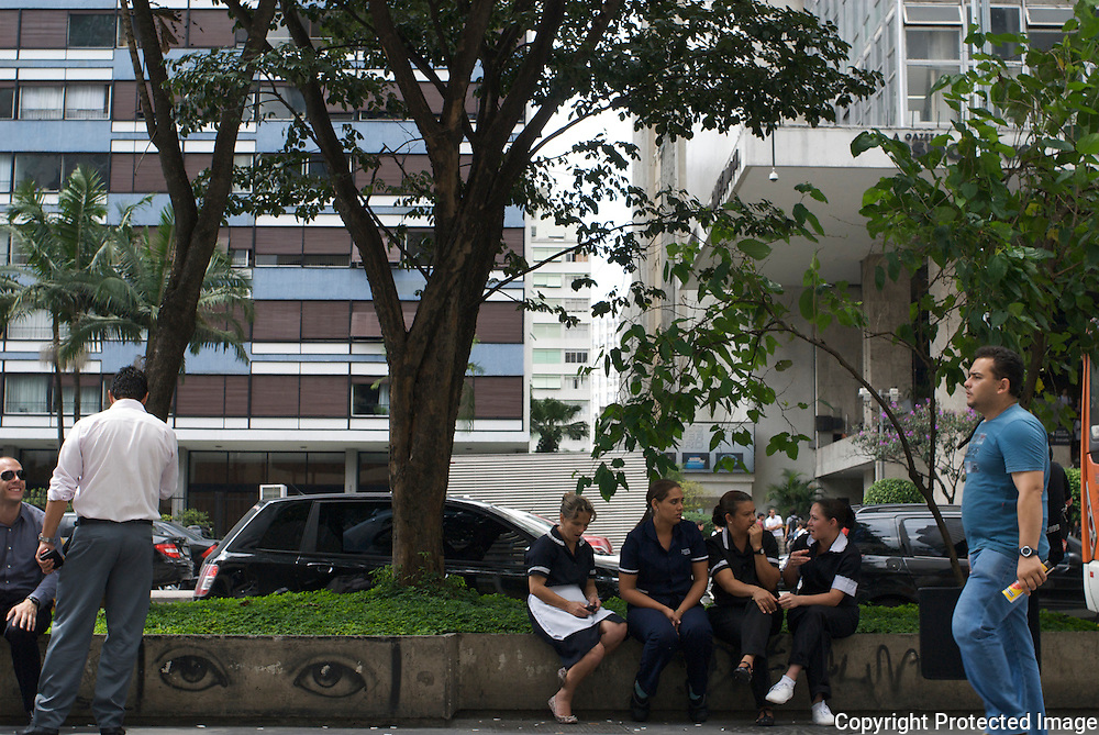 Maids in Sao Paulo sit on *Avenida Paulista during their lunch break. <br />