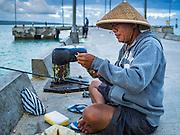 18 JULY 2016 - KUTA, BALI, INDONESIA:  A man fishes on the pier at Pasar Ikan pantai Kedonganan, a fishing pier and market in Kuta, Bali.   PHOTO BY JACK KURTZ