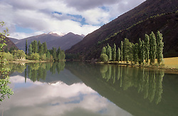 Reflections of trees and sky in lake in the Pyrenees  Embassament de la Torrassa; near Espot,