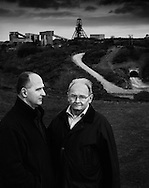 Former South Crofty miners Henry Kaczmarek (right) and his son, Mark, with the headgear of 'New Cooks Kitchen Shaft', South Crofty, in the background.