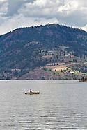 A Fisherman rowing his boat on Okanagan Lake near Ellison Provincial Park in Vernon, British Columbia, Canada