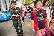 "23 JANUARY 2013 - BANGKOK, THAILAND:   A Bangkok Criminal Court security officer (left) escorts protestors off court property after Somyot Prueksakasemsuk was sentenced on ""Lese Majeste"" charges Wednesday. Somyot was sentenced to 11 years imprisonment Wednesday. He was arrested on April 30, 2011, and charged under article 112 of Thailand's penal code, which states that ?whoever defames, insults or threatens the King, the Queen, the Heir-apparent or the Regent, shall be punished with imprisonment of three to fifteen years"" after the magazine he edited, ""Red Power"" (later changed to ""The Voice of Thaksin"") published two articles by Jit Pollachan, the pseudonym of Jakrapob Penkair, the exiled former spokesman of exiled fugitive former Prime Minister Thaksin Shinawatra. Jakrapob, now living in Cambodia, has never been charged with any crime for what he wrote.     PHOTO BY JACK KURTZ"