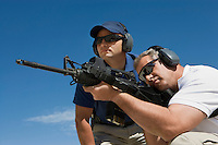 Instructor with man aiming machine gun at firing range, low angle view