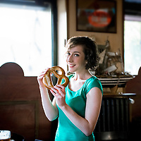 Young brunette woman about to eat a delicious pretzel, looing at camera, indoor setting