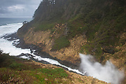 An ocean storm and one of the highest tides of the year causes water to spray high out of Devils Churn, a very narrow inlet located south of Yachats, Oregon. Pacific Ocean waves eroded the very narrow channel in the basalt. During storms and the highest tides, water erupts out of the end of the inlet.