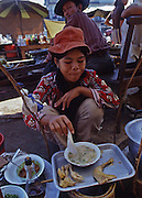 Teen age girl eats soup and chicken in outdoor market restaurant, Vientiane, Laos Asia