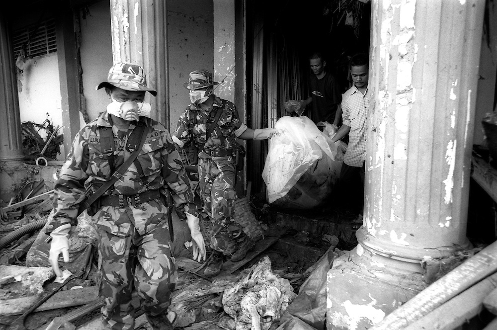 Members of the Indonesian Military, TNI, and local vollunteers remove yet another body from a shop in the Tsunami devastated city of Banda Aceh. January 4 2005.