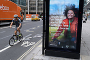 A cyclist on a foldaway bike rides past a digital ad by TFL (Transport For London) promoting cycling skills at the time of the Coronavirus pandemic - when more Londoners are taking to two wheels as an alternative to the capital's public transport system, on 6th August 2020, in London, England.