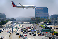 An American Airlines aircraft flies over the site of a small plane crash on on the San Diego (405) Freeway near the Wayne Airport in Orange County, California, June 30, 2017.  (Xinhua/Zhao Hanrong)(Photo by Ringo Chiu)<br /> <br /> Usage Notes: This content is intended for editorial use only. For other uses, additional clearances may be required.