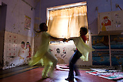 Two girls dancing during activity time at the Kamatipura Centre in Mumbai. The centre welcomes about 100 children every day from the surrounding red-light district. The centre is run by the Prerana organisation who specialise in children of the red-light districts in Mumbai.