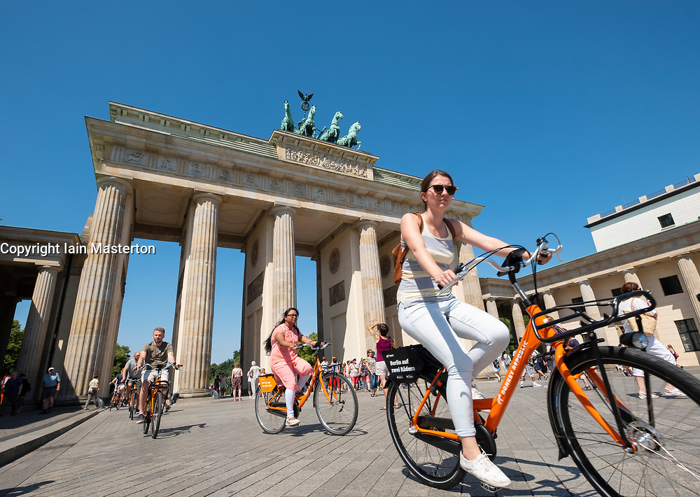 Tourists on bicycles in front of Brandenburg Gate in Berlin, Germany