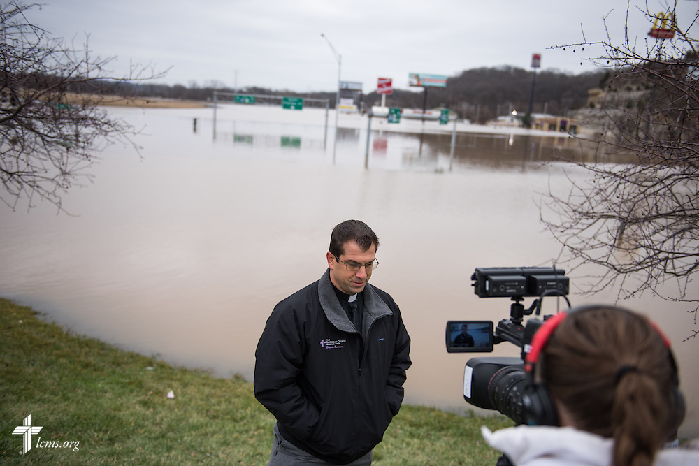 The Rev. Ross Johnson, director of LCMS Disaster Response, interviews in front of floodwaters at the intersection of Interstate 44 and Highway 141 near Fenton, Mo., on Thursday, Dec. 31, 2015, in St. Louis.  LCMS Communications/Erik M. Lunsford