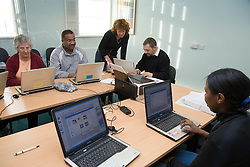 Woman teaching group of adults computer skills,