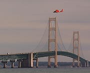 A Coast Guard helicopter departs after locating a woman in the waters of the Straits of Mackinac who either fell or jumped from the Mackinac Bridge.