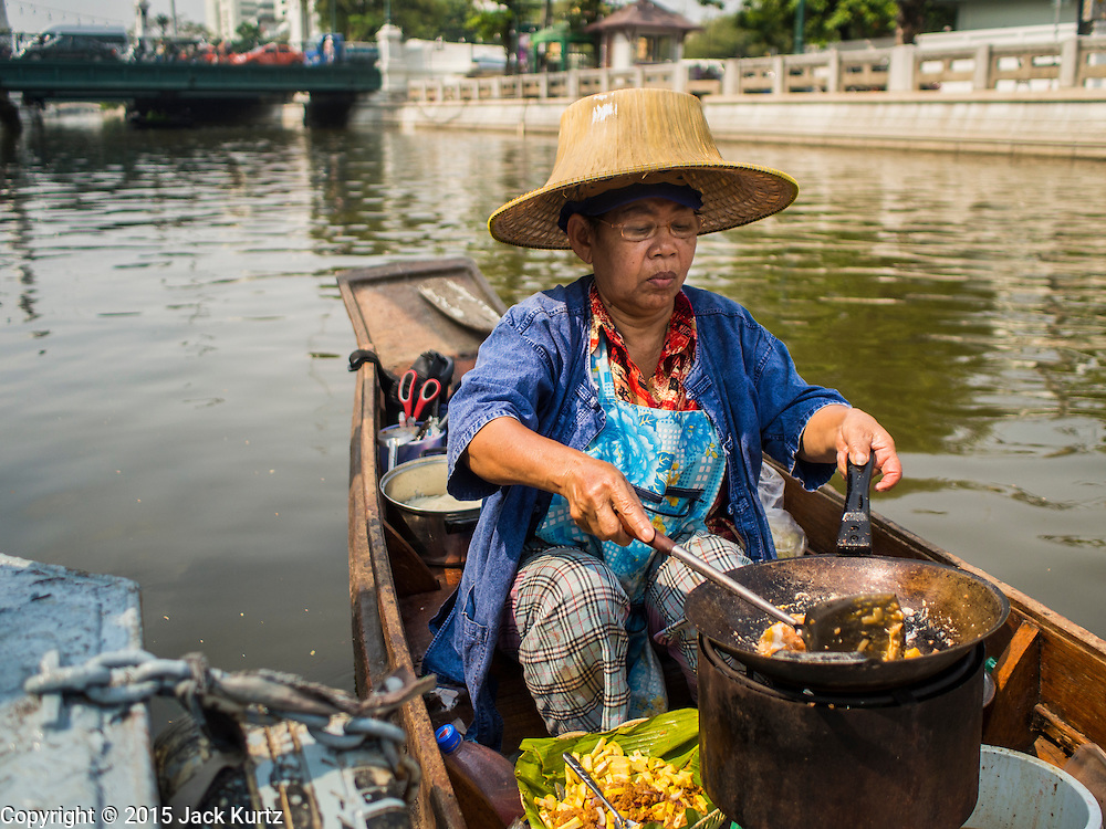"""12 FEBRUARY 2015 - BANGKOK, THAILAND:  A vendor makes """"pad Thai"""" a fried noodle dish sometimes called the national dish of Thailand, at the new floating market opened on Khlong Phadung Krung Kasem, a 5.5 kilometre long canal dug as a moat around Bangkok in the 1850s. The floating market opened at the north end of the canal near Government House, which is the office of the Prime Minister. The floating market was the idea of Thai Prime Minister General Prayuth Chan-ocha. The market will be open until March 1.   PHOTO BY JACK KURTZ"""