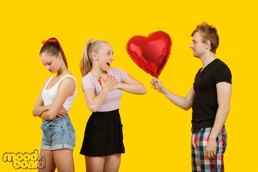 Young man gifting heart shaped balloon to surprised woman with friend feeling left out standing behind