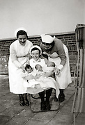 three nurses posing with newborn babies England 1930s