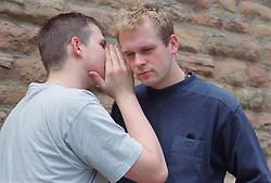 Teenage boy whispering in friend's ear,
