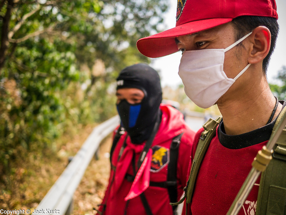 """06 APRIL 2013 - CHIANG MAI, CHIANG MAI, THAILAND: A Thai fire commander coordinates efforts to control an illegal burn that got out of control on the edge of Chiang Mai. The """"burning season,"""" which roughly goes from late February to late April, is when farmers in northern Thailand burn the dead grass and last year's stubble out of their fields. The burning creates clouds of smoke that causes breathing problems, reduces visibility and contributes to global warming. The Thai government has banned the burning and is making an effort to control it, but the farmers think it replenishes their soil (they use the ash as fertilizer) and it's cheaper than ploughing the weeds under.   PHOTO BY JACK KURTZ"""