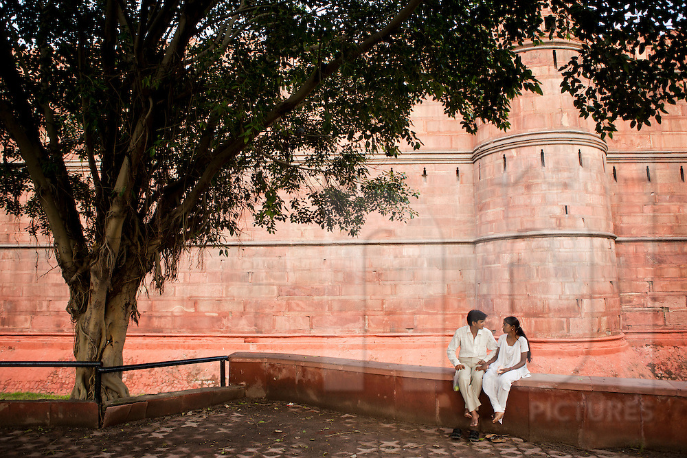 A young indian couple sit on a public square along fortifications of Red Fort, Delhi, India, Asia