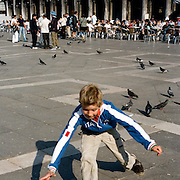 A young boy chasing pigeon's across the Piazza San Marco. Venice, Italy. 1st May 2011. Photo Tim Clayton