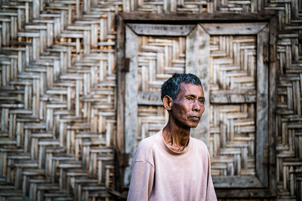 MYITKYINA, MYANMAR - MARCH 12th, 2016: Sin Hwa, 60, at his new home in Aungmyinthar Village. He was forced to move here in 2011 when the Myitsone Dam project was supposed to flood the land he lived and farmed on. In this village, there is no land for cultivation, and he's only able to do day labor jobs for income, which are inconsistent. The dam project was stalled not long after they moved, and still remains on hold. It still remains  unclear whether Myanmar's newly elected government will resume or cancel the project, which is largely unpopular in Kachin State, as it would flood large swaths of land, and the majority of electricity it would produce would be delivered to China.