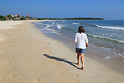 Ocean and woman walking on sandy tropical beach at Pasikudah Bay, Eastern Province, Sri Lanka, Asia