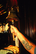 Scotland tattoo publican ringing last orders on a bell in a pub