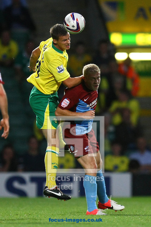 Picture by Paul Chesterton/Focus Images Ltd +44 7904 640267.28/08/2012.Ryan Bennett of Norwich and Mike Grella of Scunthorpe in action during the Capital One Cup 2nd Round match at Carrow Road, Norwich.