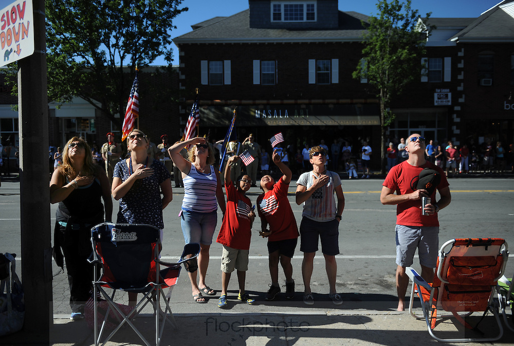 Spectators listen to the national anthem as the flag is raised before Needham's annual Grand Parade on July 4, 2016.<br /> Wicked Local staff photo / Kate Flock