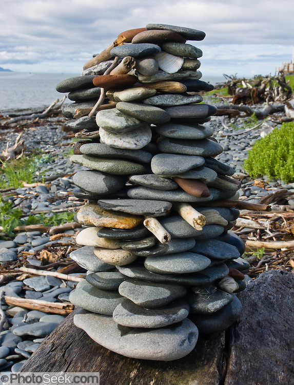 Round stones and drifwood are stacked into a cylindrical monument in Homer, Alaska, USA.