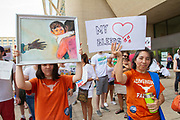 """Clara Limberg, 18, left, uses her painint """"Torn apart"""" as a protest image during the Families Belong Together rally in downtown Dallas. Her mother Kim, right, attended to protest man's inhumanity to man. What is happening is totally against everything this country represents."""" she said."""