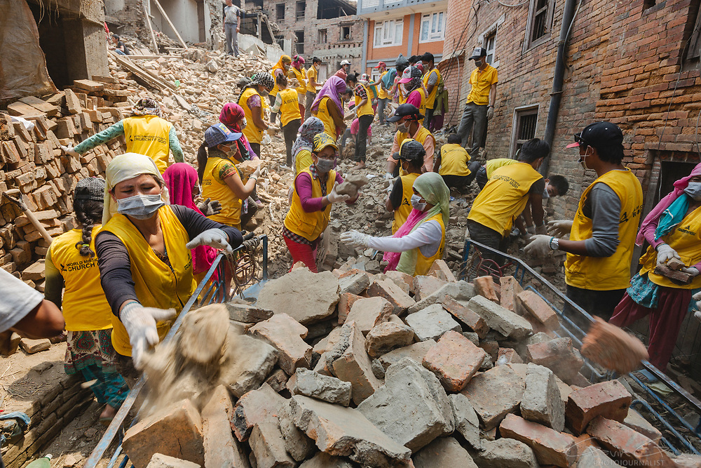 Volunteers with the World Mission Society help to clear rubble from buildings destroyed by the 2015 Nepal earthquake.