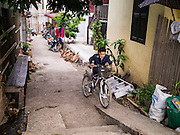 11 MARCH 2013 - LUANG PRABANG, LAOS:  A boy on his way to school pushes his bike up a narrow alley in Luang Prabang, Laos.   PHOTO BY JACK KURTZ